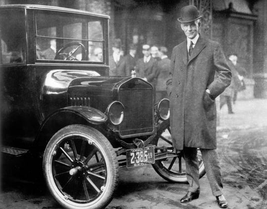 Henry Ford next to a Model T in 1921.