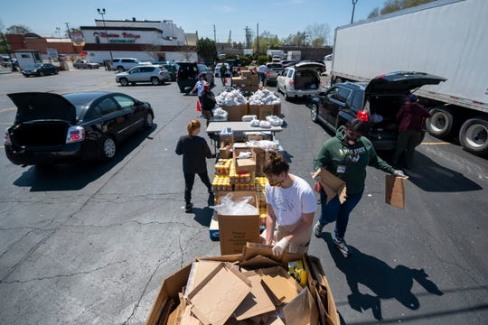 Workers load food into vehicles during a Gleaners food bank pop-up in cooperation with the Roberto Clemente center, in southwest Detroit, May 6, 2020.