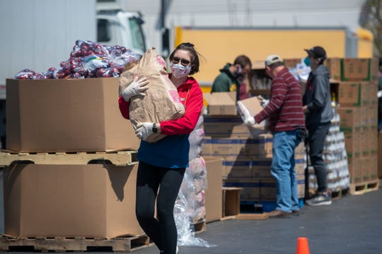 Stephanie Hough, a temporary worker for Gleaners, helps prepare before the start of a food bank pop-up in cooperation with the Roberto Clemente Center in southwest Detroit, May 6, 2020.