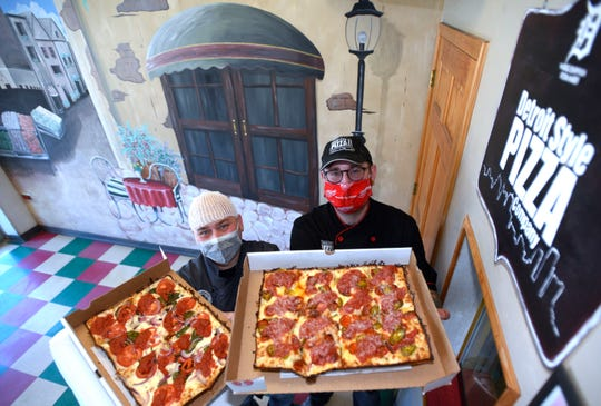 Detroit Style Pizza Company co-owners Shawn Randazzo, left, and Joe Maino pose with the Margherita In The D Pizza and the Harper Hornet pizza, respectively.