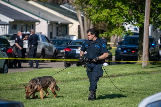 A member of the Michigan State Police canine team searches a yard on John Daly near Lehigh in Inkster on May 6, 2020. A young boy was found stabbed to death in the home.