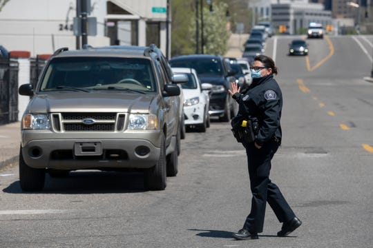 Detroit police officer A. Kellogg directs traffic for the hundreds of vehicles expected for a Gleaners food bank pop-up in cooperation with the Roberto Clemente center, in southwest Detroit, May 6, 2020.
