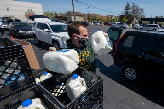 Temporary employee Kiera Scott prepares to load milk into vehicles during a Gleaners food bank pop-up in cooperation with the Roberto Clemente center, in southwest Detroit, May 6, 2020.
