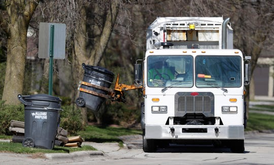 Crews collect garbage from St. Francis Drive on May 6, 2020, in Allouez, Wis.