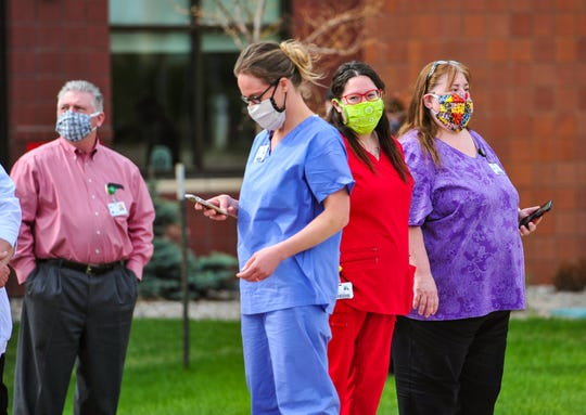 Great Falls Clinic staff members, wearing their face masks, gather in front of the hospital building to watch Montana Air National Guard C-130's perform a flyover to show appreciation for the medical community of Great Falls on Wednesday, May 6, 2020.