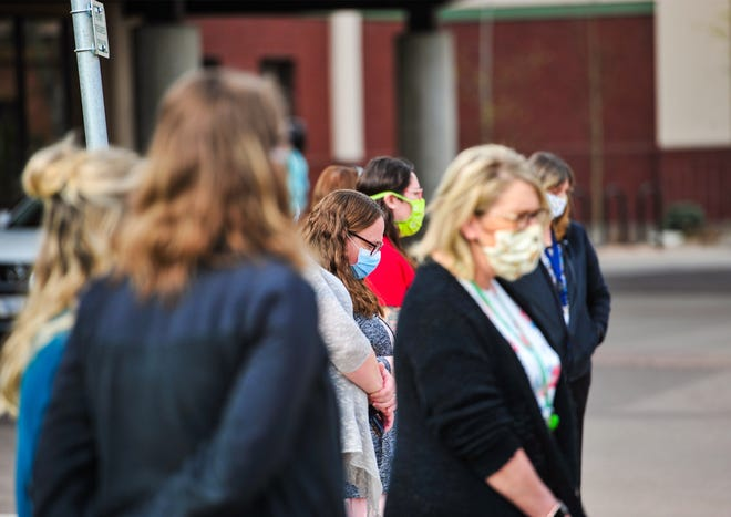 Great Falls Clinic staff members, wearing their face masks, gather in front of the hospital building to watch at Montana Air National Guard C-130's perform a flyover to show appreciation for the medical community of Great Falls on Wednesday, May 6, 2020.
