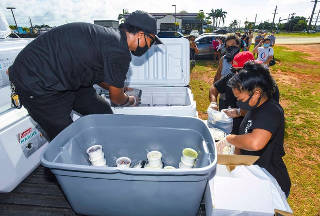 KÅDU House Guam employees bag containers of food for a residents lined up in Dededo for a KÅDU Caregivers Donation Program food distribution event in the parking lot of the Dededo Mall on Wednesday, May 6, 2020.