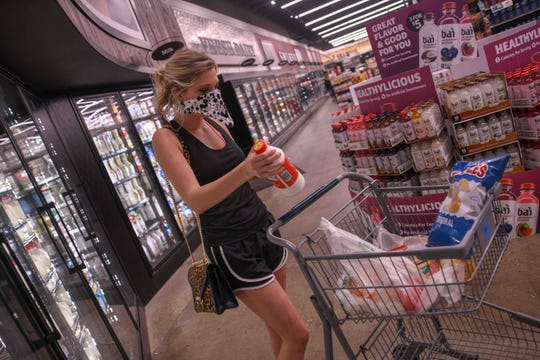 Tyler Jones wears a mask while she shops for groceries at the Midtown Corner Market amid the COVID-19 outbreak in Hattiesburg, Miss., Wednesday, May 6, 2020.