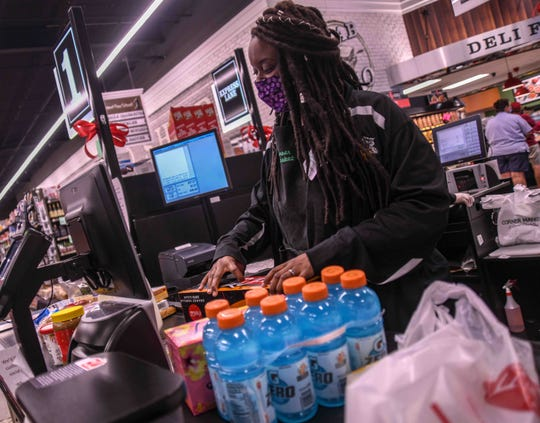Corner Market employee Zhane' Thorton wears a mask while checking out a customer amid the COVID-19 outbreak in Hattiesburg, Miss., Wednesday May 6, 2020.