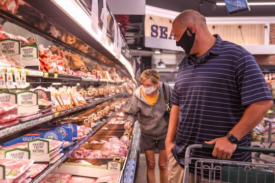 Corner Market customers Ricky Davis, right, and Valerie Simmons shop with masks on during the COVID-19 outbreak at the midtown location in Hattiesburg, Miss., Wednesday, May 6, 2020.