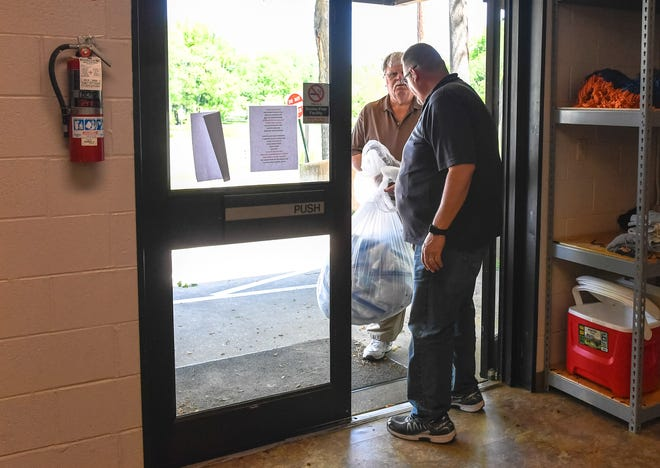 Bruce Farmer delivers a bag of 1,000 surgical masks to Gathering Place director Bill Rhodes as part of an effort by the Henderson County Emergency Management Agency to get face masks in the hands of residents, free of charge, Wednesday, May 6, 2020.