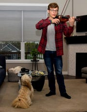 With his dog Coco apparently enchanted, West High School sophomore Liam Edberg logs practice time at home for his online YouTube charity performance through Cadenza Music Club. He will appear in duet, trio and quartet videos for the fundraising project.