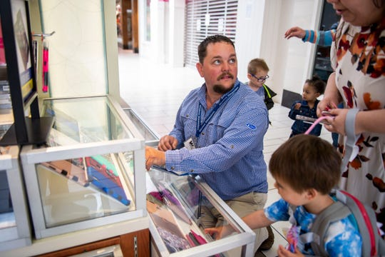 Steven Rich helps a customer pick out a phone case at his Kiosk store in Old Hickory Mall in Jackson, Tenn., Wednesday May 6, 2020.