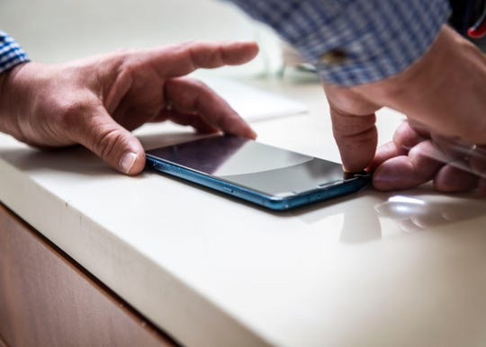 Steven Rich places and adjusts a glass shield on a customer's phone at the Old Hickory Mall in Jackson, Tenn., Wednesday May 6, 2020