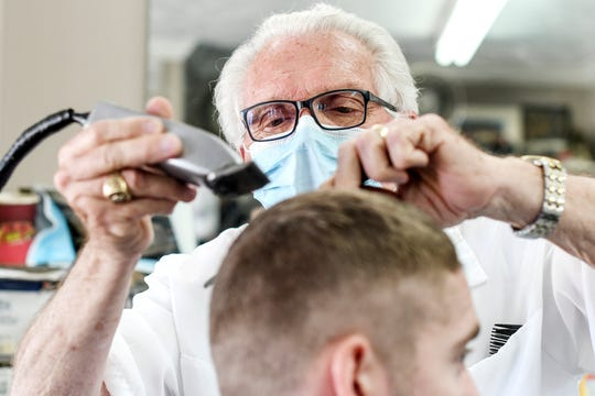 Karl Manke cuts the hair of Tim Lundy, of Owosso, at Karl Manke's Barber and Beauty Shop on Wednesday, May 6, 2020, in Owosso. Lundy has been getting his hair cut by Manke his entire life.