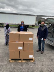 Pictured with boxes of shields areFarhiyo Alasow (left) and Darrell Finck (right) of Alene Candles, Tabitha Butcher (center) ofMarion County Board of DD.