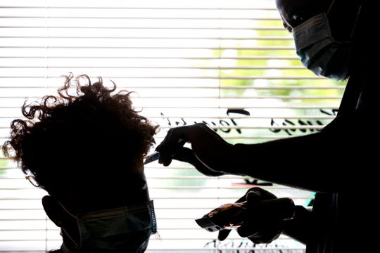 Jurek Williamson, the owner of King's Temple Barber Shop in Memphis, cuts the hair of Dashawn Whiting, 16, on the first day he is able to reopen his shop during Phase 1 of the city's plan to restart the economy after it was shuttered over fears stemming from spread of the coronavirus pandemic.