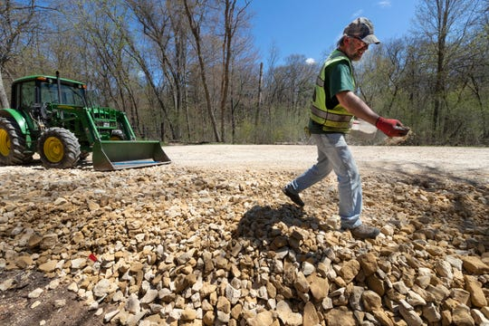 "DNR employee Gerry Schneider spreads lawn seed while working on expanding a parking area to access the Fern Dell Gorge hiking trail during ""cleanup day"" at Mirror Lake State Park in Baraboo."