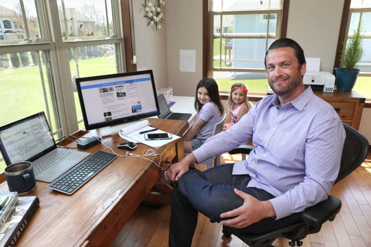 Jim Jeffers, of Robert Half's Milwaukee office, is working from his Muskego home.  His daughters Aubrey, 6, center, and Amelia, 3, have also set up a home office next to their father's.