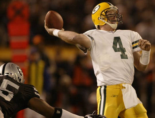 Green Bay Packers Brett Favre throws a touchdown pass to Wesley Walls while being pressured by Oakland Raiders Lorenzo Bromell during the first quarter of their game Monday, December 22, 2003 at Network Associates Coliseum in Oakland, Calif.(Milwaukee Journal Sentinel photo by Tom Lynn)