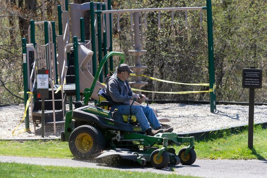 "DNR worker Steve Jarvis mows the playground and beach area during ""cleanup day"" Wednesday at Mirror Lake State Park in Baraboo."