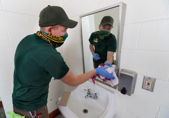 Wisconsin Department of Natural Resources employee Trevor Hines deep cleans a bathroom Wednesday at Mirror Lake State Park in Baraboo. State parks are closed on Wednesday for cleaning.