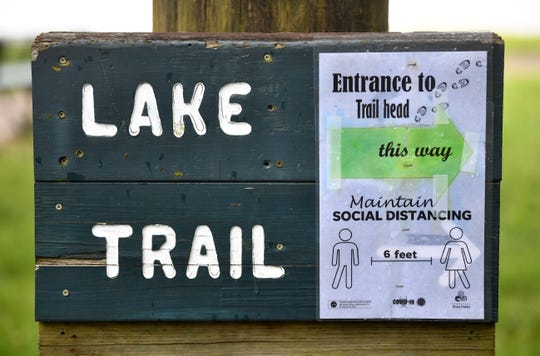 Signs encourage visitors to stay six feet apart as they enjoy being outdoors at Long Hunter State Park.