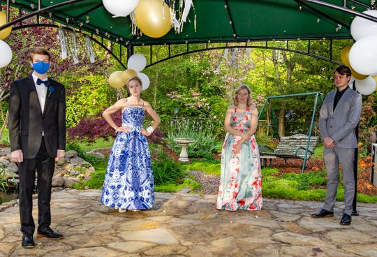 (From left) Karson Lewis, Sage McClung, Kate McClung, and Trevor Cox practice social distancing during a backyard prom at home.