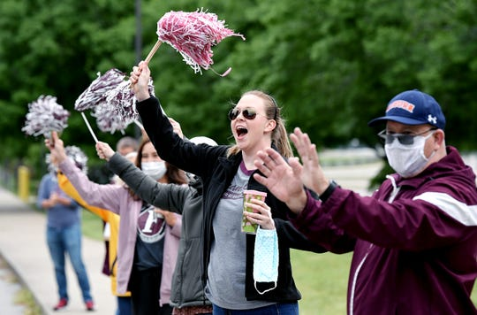 Franklin High staff and teachers like Tricia Swift cheer as graduating seniors  pick up their caps and gowns at the school in Franklin on Wednesday, May 6, 2020.