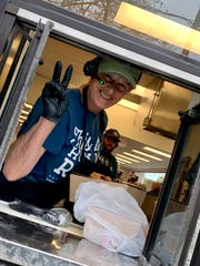 A worker at the new Loveless Biscuit Kitchen drive-thru window poses for a picture before serving to go food.