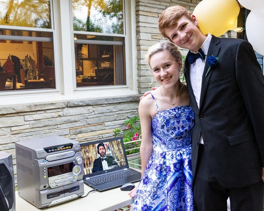 """(Left) Karson Lewis and Sage McClung, Franklin High School seniors, celebrated prom in McClung's backyard, while watching """"Some Good News"""" Prom 2020 with host and actor John Krasinski on You Tube."""