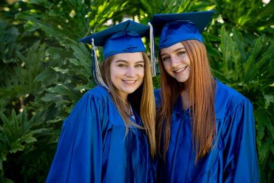 Heather Howard, 18, left, and Lauren Howard, 18, right, seniors at Barron Collier High School, pose for a portrait in their caps and gowns at their home in Naples on Tuesday, May 5, 2020.