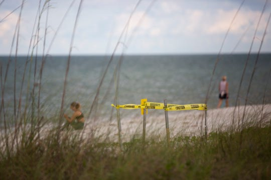 Caution tape marks a sea turtle nest near the beach access point at Fourth Avenue North in Naples on Wednesday, May 6, 2020.