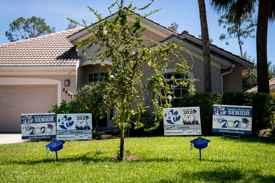 Yard signs in the front lawn congratulate Heather and Lauren Howard on their graduation from Barron Collier High School at their home in Naples on Tuesday, May 5, 2020.