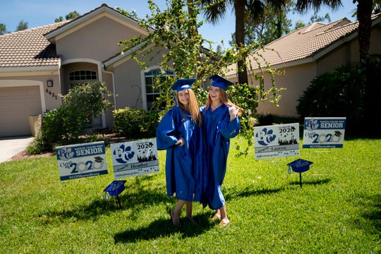 Heather Howard, 18, left, and Lauren Howard, 18, right, seniors at Barron Collier High School, pose for a portrait in their caps and gowns at their home in Naples on Tuesday, May 5, 2020. Yard signs in the front lawn from their mom, school, and church congratulate them on their high school graduation.