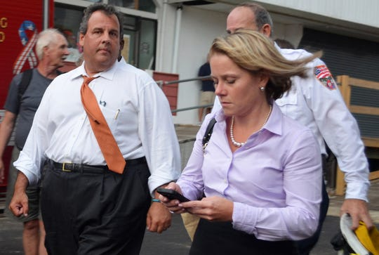 New Jersey Governor Chris Christie (C) and Deputy Chief of Staff Bridget Anne Kelly (R) walk at the scene of a boardwalk fire September 12, 2013 in Seaside Heights, New Jersey.  According to reports January 8, 2014, Christie Deputy Chief of Staff Bridget Anne Kelly is accused of giving a signal to the Port Authority of New York and New Jersey about  two weeks before two lanes of the George Washington Bridge, allegedly as punishment for the Fort Lee, New Jersey mayor not endorsing the Governor during the  election.