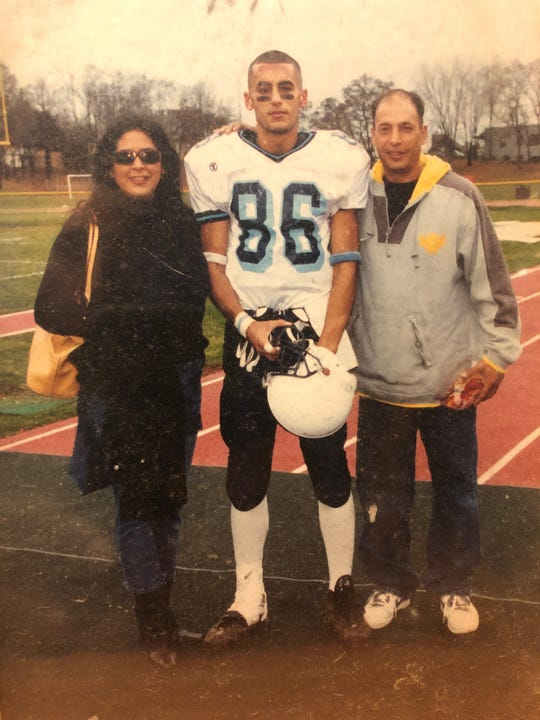 Palisades Park's Orestes Medina Jr., middle, poses with his parents, Haymee Medina and Orestes Medina Sr. at the Thanksgiving Day game versus Bergen Tech in 2004.