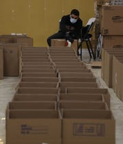 Mohammad Deeb 23 of Clifton tapes boxes to pack donated food at the Palestinian American Community Center that has transformed its mission from an education, culture and recreation center to a headquarters for COVID relief, giving out PPE, meals and food boxes.