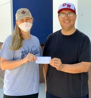 Chelsea McGinnis presented Deming High School Athletic/Activities Director Bernie Chavez with a check for $1,700 to help support the Frank Dooley DHS Scholarship Fund.