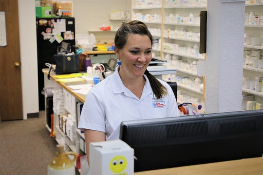 Pharmacist Ashley Seyfarth checks a prescription for a customer from behind the counter at Kare Drug in Aztec.