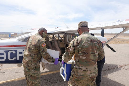 Members of the New Mexico National Guard load COVID-19 test samples into an airplane on Wednesday, May 6, 2020, at Four Corners Regional Airport in Farmington. The test samples were flown out to Albuquerque and delivered to a laboratory being run by the New Mexico Department of Health.