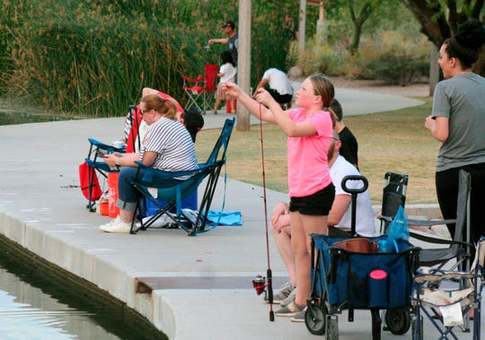 In this April 30, 2020 photo, a girl checks her line as people fish at Veterans Oasis Park in Chandler. Many state fishing programs have continued to stock community lakes during the coronavirus pandemic, allowing people who have been locked up for weeks a chance to enjoy the outdoors.