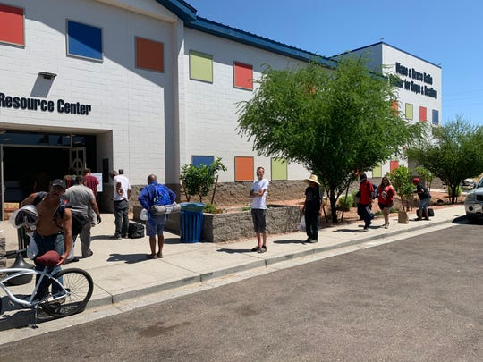 Clients of The Society of St. Vincent de Paul stand in line, the proper distance apart, to pick up meals.