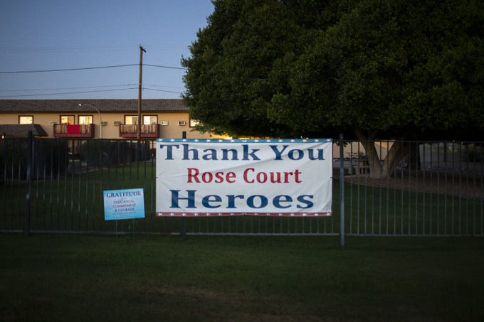 "A sign reading ""Thank You Rose Court Heroes"" hangs over the fence at the Rose Court Assisted Living & Memory Care nursing home in Phoenix on May 5, 2020. The nursing home has reported 16 cases of COVID-19 and three deaths."