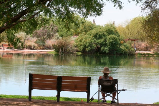 In this April 30, 2020 photo, a fisherman watches his line from the shade at Veterans Oasis Park in Chandler. People who have been locked down during the coronavirus have been turning to fishing at community lakes as a chance to go outdoors and still following social-distancing guidelines.