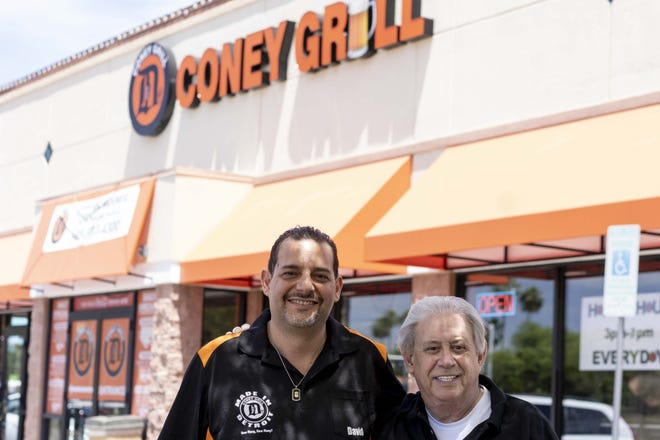 David Najor, on left, and Dr. Merrill Stromer, owners of Detroit Coney Grill, stand in front of the restaurant on May 6, 2020, after the city told them they had to take down the orange awnings outside. City officials said the orange color did not adhere to design guidelines for the city.