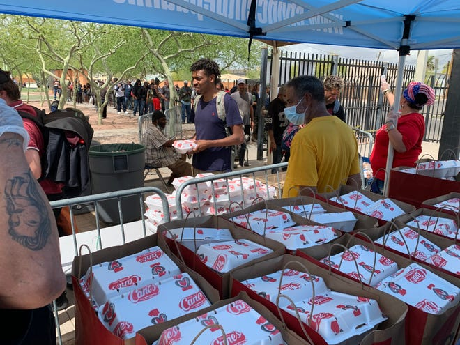 Meals purchased from local restaurants are handed out in May outside the five dining rooms at The Society of St. Vincent de Paul.