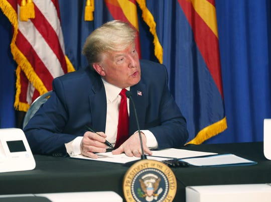President Donald Trump signs a proclamation designating May 5, 2020, as Missing and Murdered American Indians and Alaska Natives Awareness Day during a roundtable discussion at Honeywell International's mask-making operation in Phoenix.