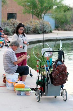 In this April, 30, 2020 photo, a couple sets up their lines to fish at Veterans Oasis Park in Chandler.