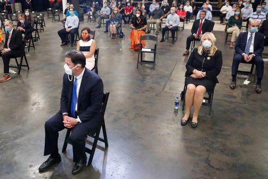 El gobernador de Arizona Doug Ducey (al frente), la senadora Martha McSally (atrás izquierda) y la representante Debbie Lesko (derecha) usan máscaras mientras esperan que el presidente Trump hable en la empresa Honeywell en Phoenix el 5 de mayo de 2020.